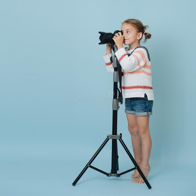 Little girl standing on her toes looking in the camera on tripod, taking picture stock photo