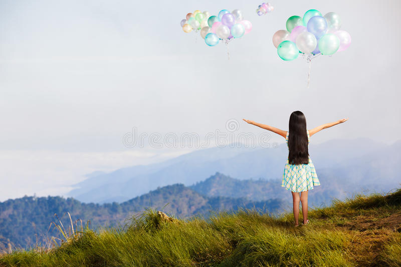 Little girl standing at high mountain and looking balloon. In the sky, Freedom concept stock photos