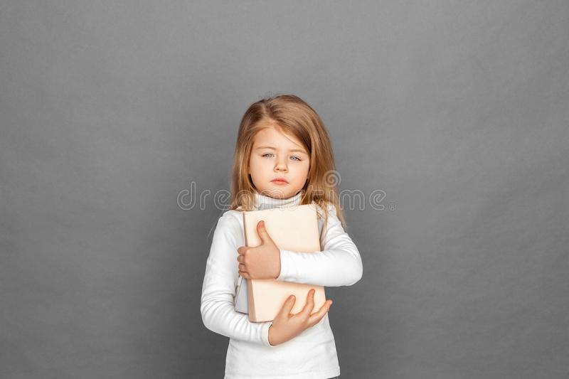 Freestyle. Little girl standing isolated on grey with books pensive stock image