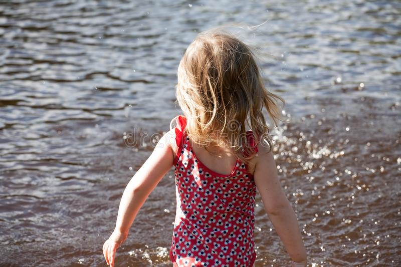 Little girl standing before lake water surface stock images