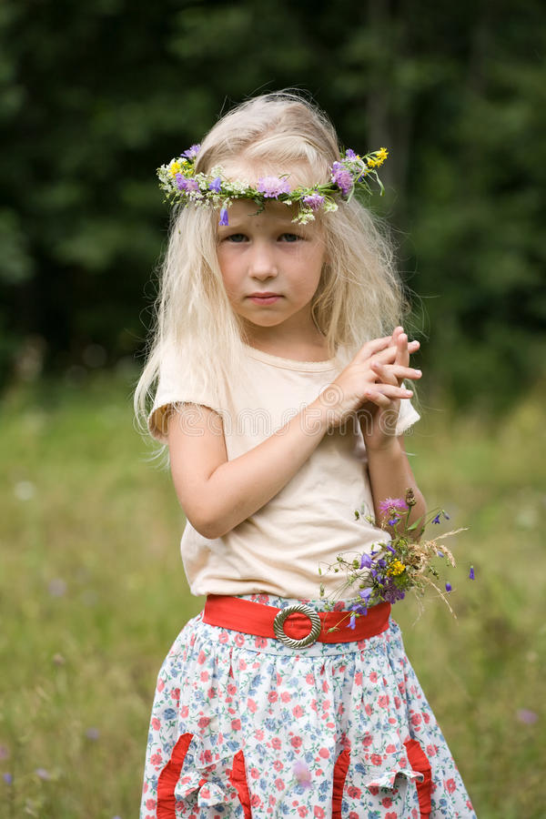 Little girl standing at the meadow stock photography