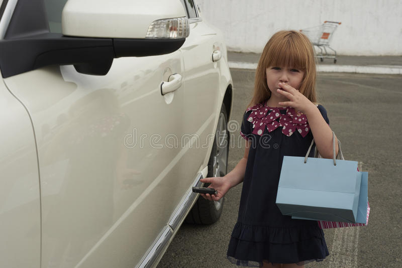 A little girl standing near a car royalty free stock photos