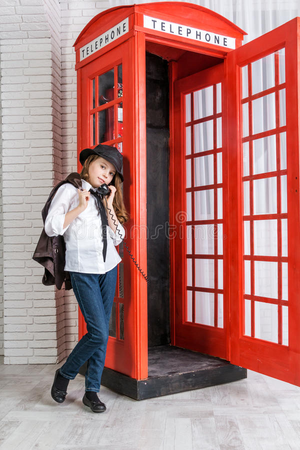 Little girl standing next to a phone booth royalty free stock image