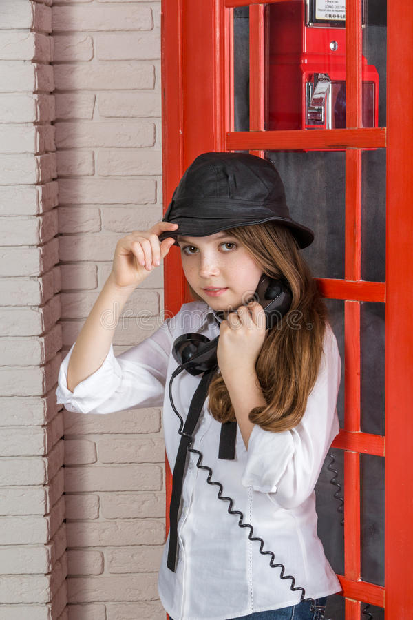 Little girl standing next to a phone booth stock image