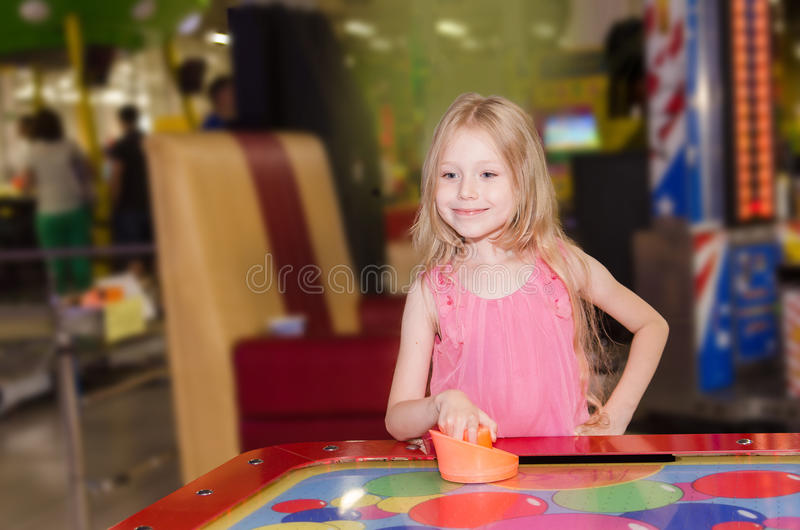 Little girl standing and playing air hockey at indoor amusement park stock image