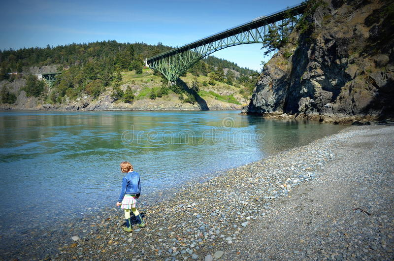 Little girl standing on shingle beach. Little girl on shingle beach at Deception Pass, Washington Bridge with river flowing by royalty free stock images