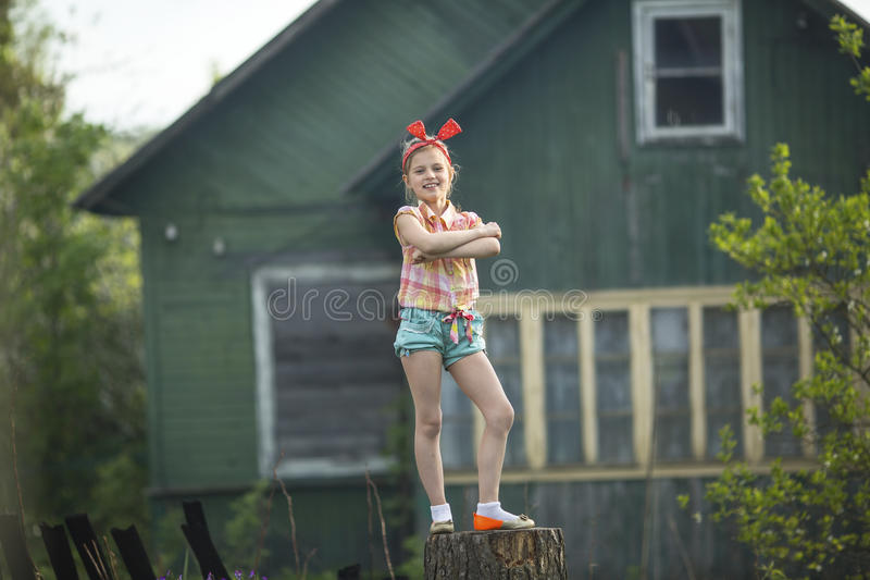 Little girl standing on a stump near the country house. royalty free stock photo