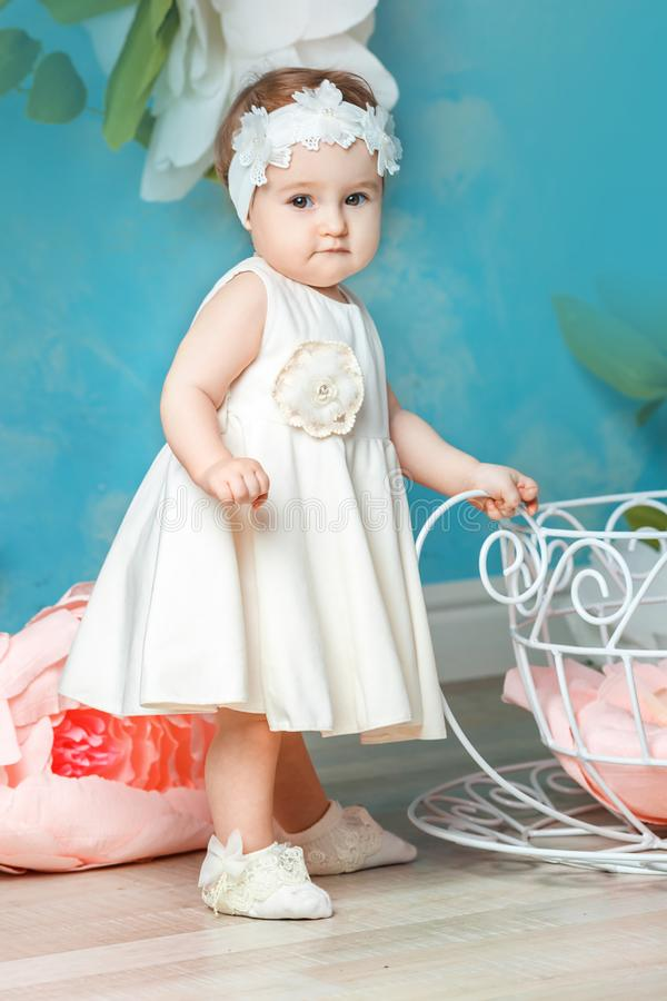 Little girl standing in a white dress stock photography