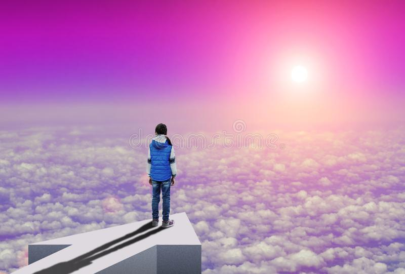 Little girl stands above the clouds and looks how sun rising over the horizon royalty free stock images