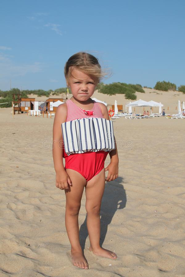 Little girl stands on beach in a special swimsuit for children who can not swim. child in swimsuit, which he kept afloat. Portrait, outdoor, sun, 3, recreation royalty free stock photography