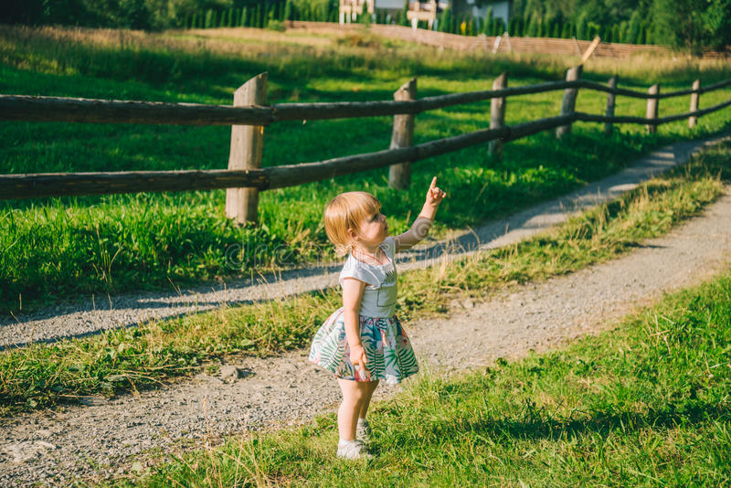 Little girl stands on the country raod and point on somtheing stock photography