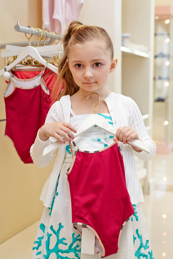 Little girl stands holding hanger with swimsuit