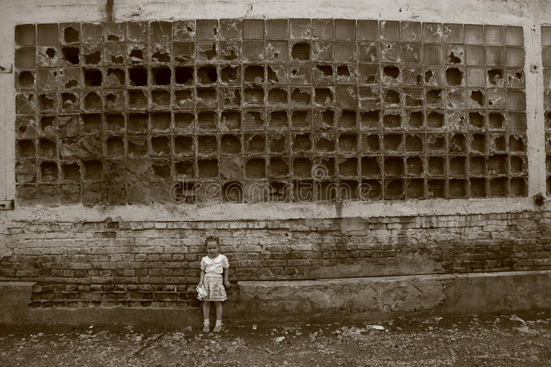 Little girl stands near the destroyed wall royalty free stock images
