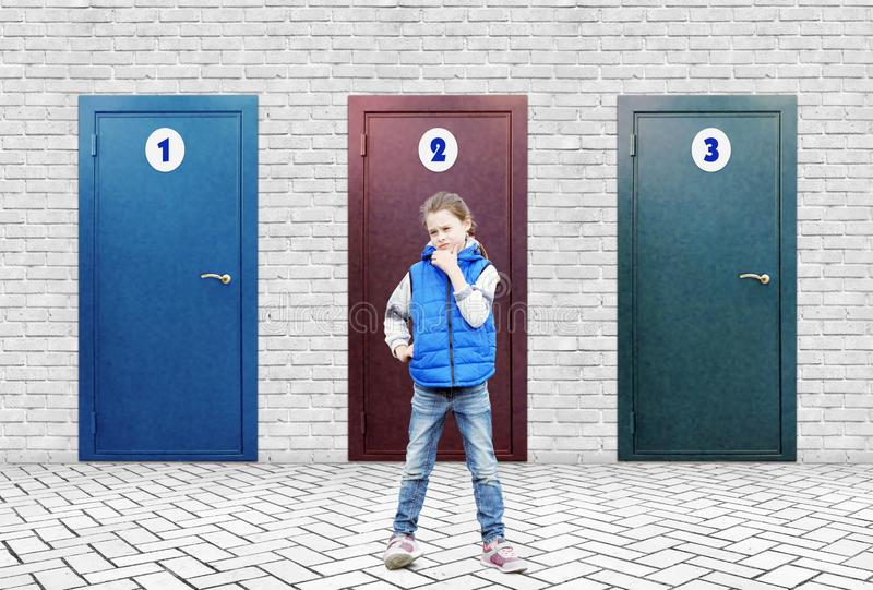 Little girl stands near a high brick wall in which three doors with different numbers stock photo
