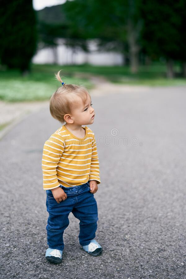 Free Little Girl Stands On The Gravel Path In The Park And Looks Away Stock Images - 221470584