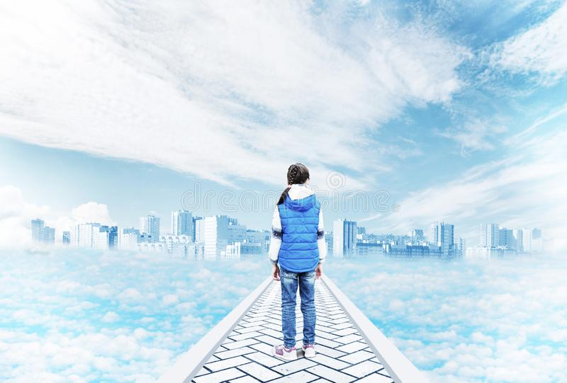 Little girl stands on the road to a mystical city in the sky among the clouds stock image