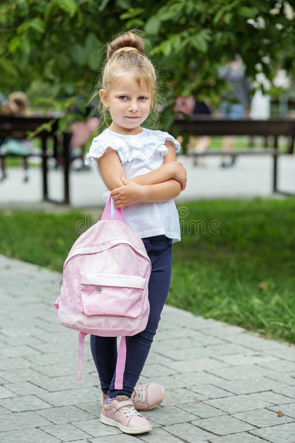 Little girl stands sad with a backpack. The concept of school, study, education, childhood.  royalty free stock images