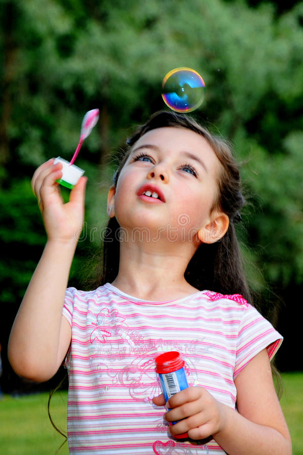 The little girl starts up soap bubbles stock photos