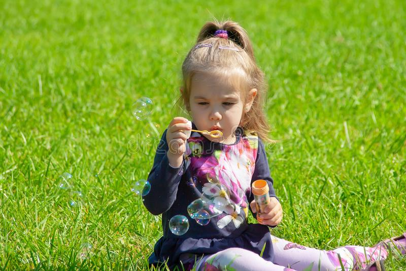 The little girl starts up soap bubbles in the park stock image