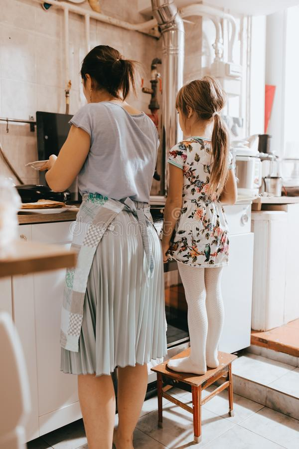 Little girl staying on the stool next to her mother is cooking pancakes for the breakfast in the little cozy kitchen royalty free stock image