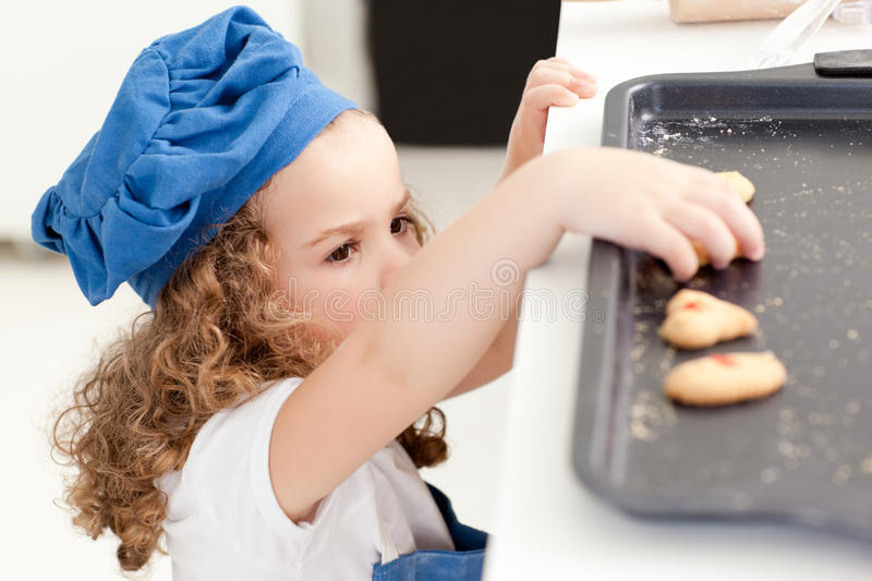 Little girl stealing cookies stock image