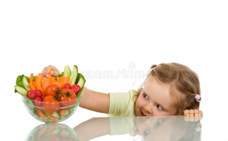 Little girl stealing vegetables