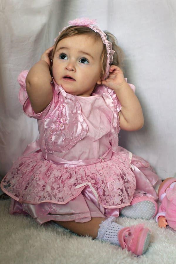 Little girl straightens headband. Little girl in a pink dress straightens headband stock image