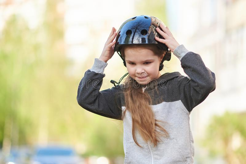 A little girl straightens her helmet while riding a skateboard. For any purpose stock photo