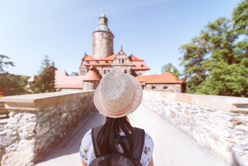 Little girl in a straw hat and backpack in front of the bridge royalty free stock photography