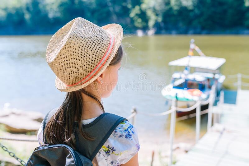 Little girl in a straw hat and backpack on the river bank royalty free stock image