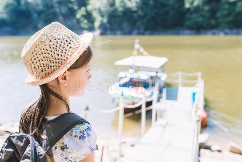 Little girl in a straw hat and backpack on the river bank stock images