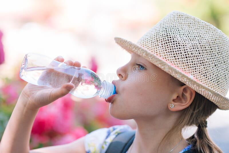 Little girl in a straw hat drinking water royalty free stock images