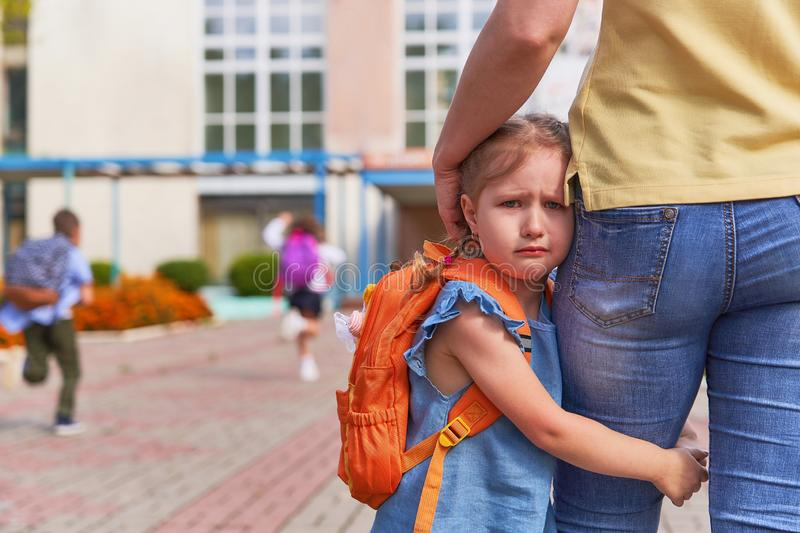 The little girl stress she does not want to leave her mother. Mother accompanies the child to school. mom supports and motivates the student. the little girl stock photography