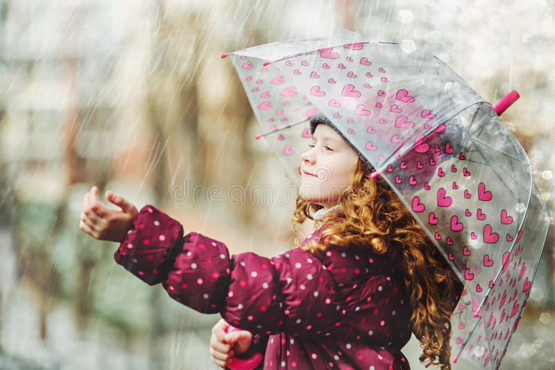 Little girl stretches her hand to catch falling raindrop. stock photos