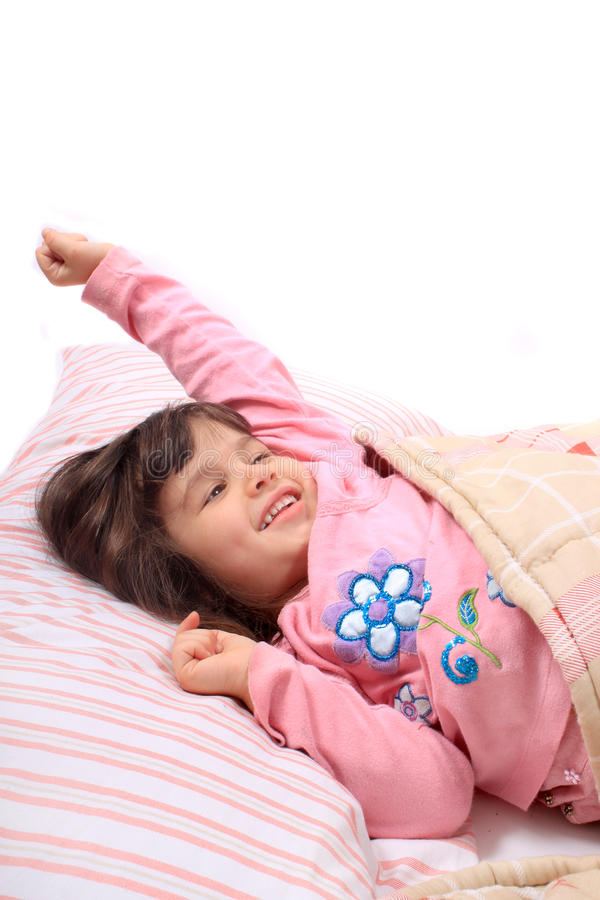 Little girl stretching in bed stock images