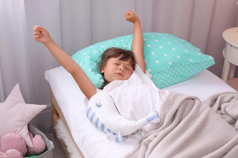 Little girl stretching in bed at home. stock images