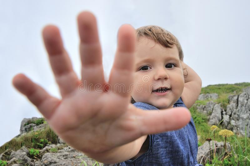 Little girl is stretching her hand to camera stock photo