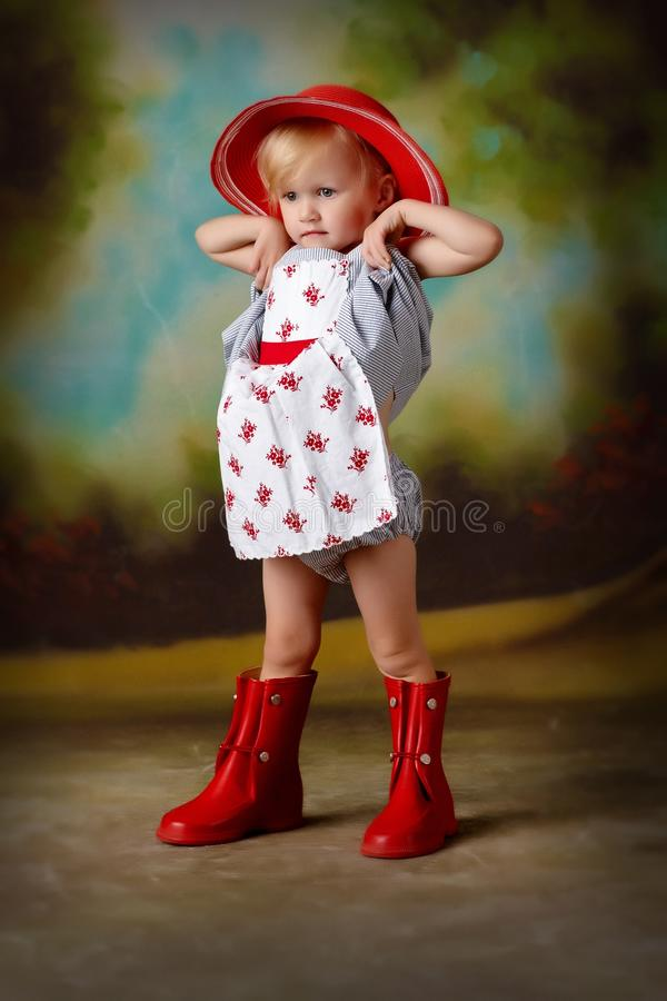 Little girl stretching in red dress. Girl little dress stretching stock photo