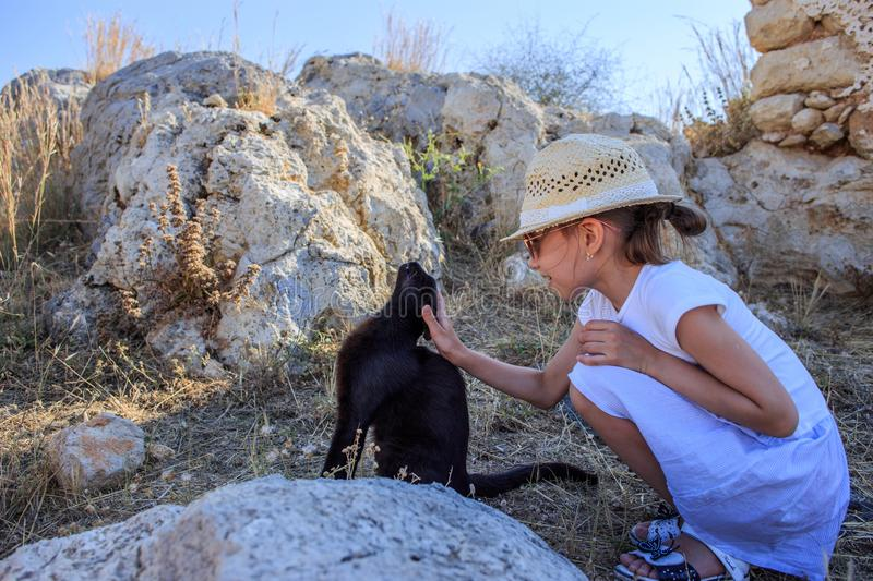 A little girl strokes and feeds a homeless black cat for a walk in the mountains by the sea.  stock photography