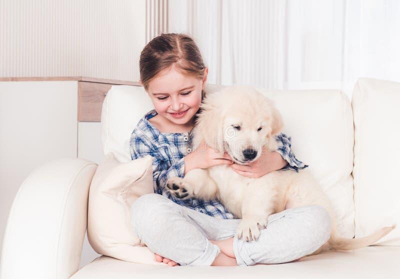 Little girl stroking puppy. Little girl stroking fluffy puppy on sofa stock photos