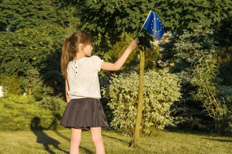 Little girl student holding European Union flag, in the park, back stock image