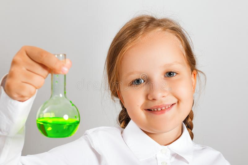 Little girl student holds in his hand a flask with liquid and looks at the camera. A child is conducting a chemical experiment.  stock photography