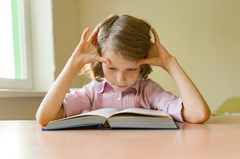 Little girl student sits at a desk with book. School, education, knowledge and children. royalty free stock photo