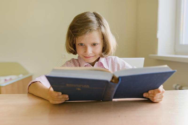 Little girl student studying at desk with book stock images