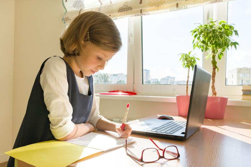 Little girl student studying sitting at her desk, girl writes in school notebook. School, education, knowledge and children stock image