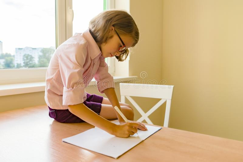 Little girl student studying sitting at her desk, girl writes in school notebook. School, education, knowledge and children stock photo