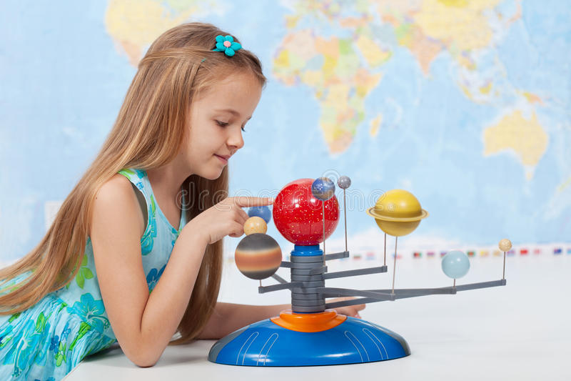Little girl studies the solar system in geography class. Looking at the scale model of planets stock images
