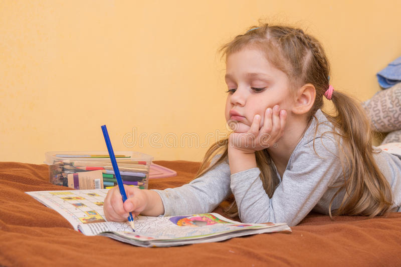 Little girl studying a magazine with pencil in his hand lying on his stomach and his head in his second hand stock photography