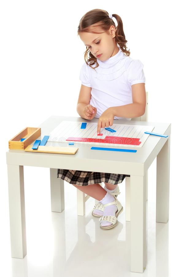 A little girl is studying Montessori stuff. A little girl in Montessori kindergarten sits at a table and studies Montessori stuff. The concept of school and royalty free stock photo