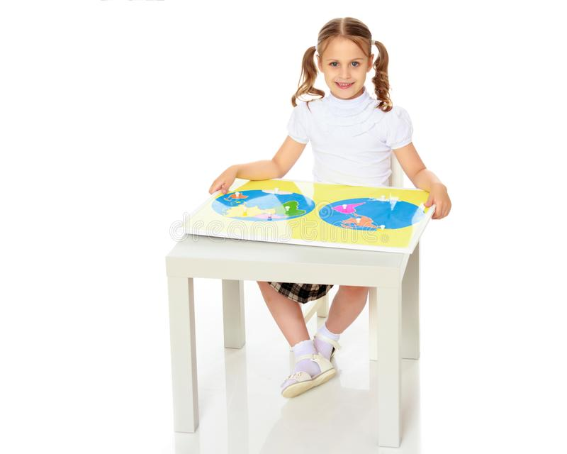 A little girl is studying Montessori stuff. A little girl in Montessori kindergarten sits at a table and studies Montessori stuff. The concept of school and royalty free stock photos